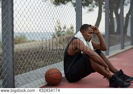 Young thoughtful african sportsman sitting on sports court with basketball ball. Black man with towel wear sportswear and sneakers. Urban basketball player. Daytime