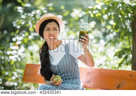 Displeased Asian Woman Grimacing While Looking At Smoothie In Plastic Cup