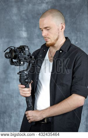 A Young Professional Videographer In A Black Shirt Holds A Professional Camera On A 3-axis Gimbal St