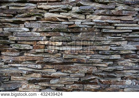 The Masonry Wall Is Made Of Flat Small Stones.
