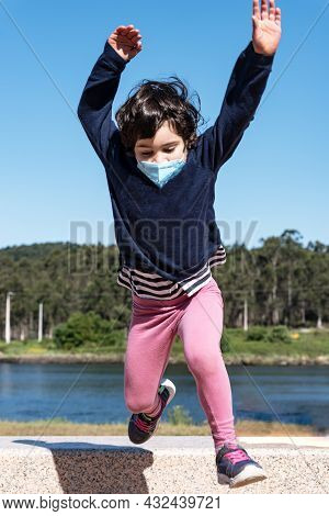 Caucasian Child Jump At Grass From The Bench On The Promenade With Smile Face