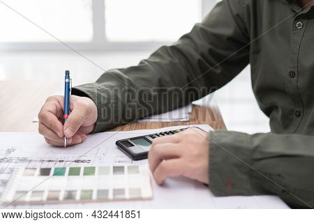 A Man Use Pencil Write In Drawing In Engineering Work  With Calculator Paint Chart And Drawing On Ta