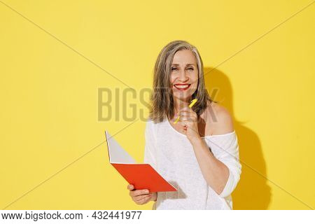 White senior woman smiling while posing with exercise book isolated over yellow wall