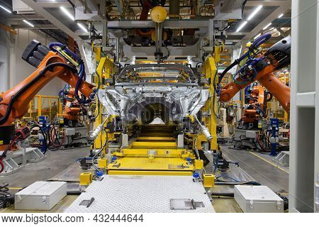 The Robot Makes Welding Of The Car Body. Assembly Line. Automobile Plant.