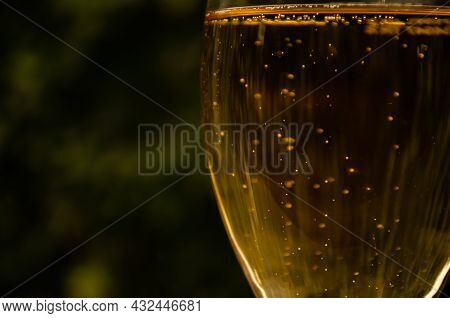 Glass Of Beer On Green Blurred Background. Bubbles Rise In Beverage. Alcohol Consumption Concept. Go