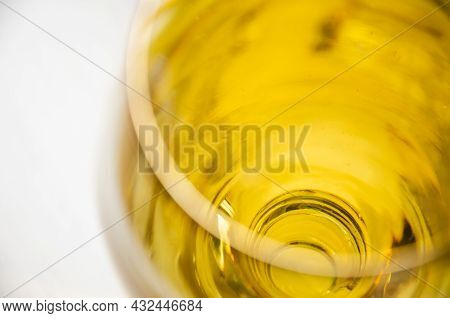 Close-up Glass With Liquid Isolated On White Background With Copy Space. Top View Glass With Golden