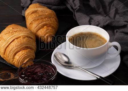 Fresh Croissants With Jam And Coffee On Dark Background. French Breakfast.