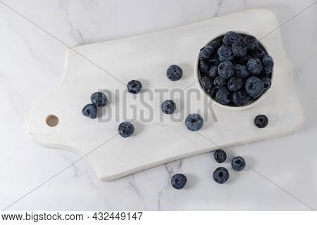 Blueberries In A Bowl On A White Wood Board.