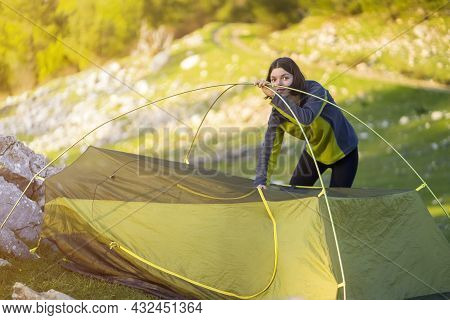 A Young Girl Sets Up Her Tent At A Campsite On A Green Meadow Among The Mountains On A Warm Summer E