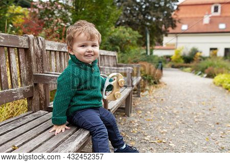 Smiling Little Boy Walking In The Park. Lovely Little Boy Playing With Wooden Car Outdoor.