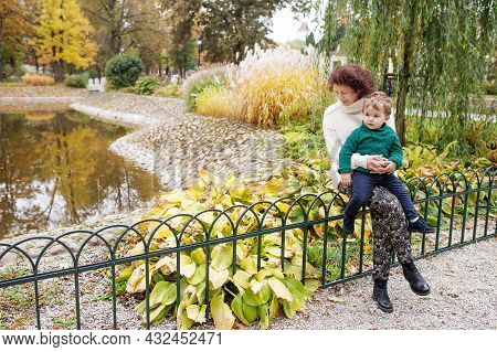 Happy Mother And Her Little Child. Cute Child Sitting With Mother In The Park. Mother And Son Embrac