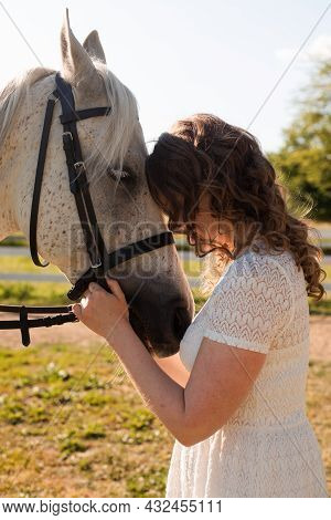 The Woman With Curly Hair Huddles To Her Horse