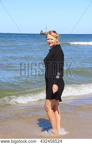 Young Woman Enjoying Resting By Sea. Girl Standing On Sandy Beach. Girl Standing In Sea Waves With V