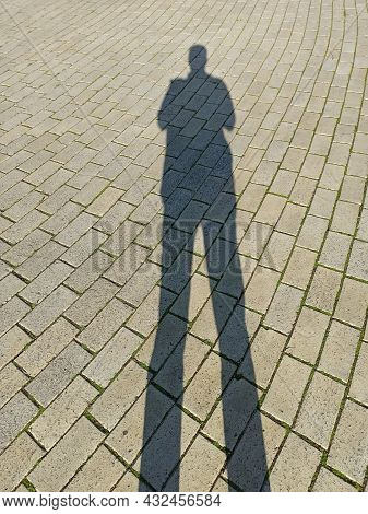 Shadow Of Man On The Road. Human Silhouette On The Pavement. High Shadow Of A Man On The Pavement