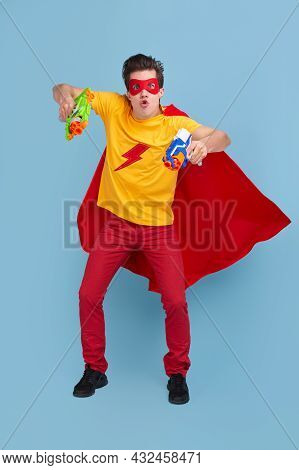 Full Body Of Brave Young Male In Superhero Cape And Mask Pretending To Fight With Colorful Plastic T