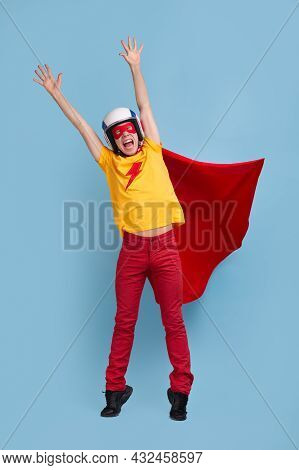 Full Body Excited Young Male In Bright Superhero Costume With Mask And Helmet Raising Hands While Pr
