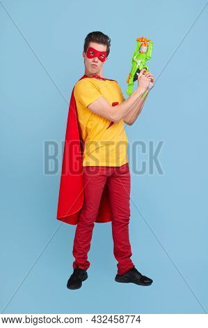 Full Body Self Assured Young Man In Superhero Costume Pointing Up With Toy Pistol And Looking At Cam