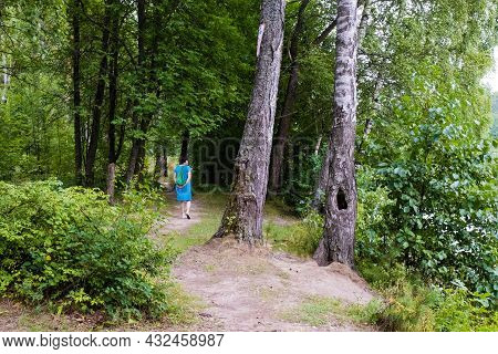 Ivanovo, Ivanovo Region, Russia - 17.08.2021: A Woman In A Blue Dress And With A Green Backpack Walk