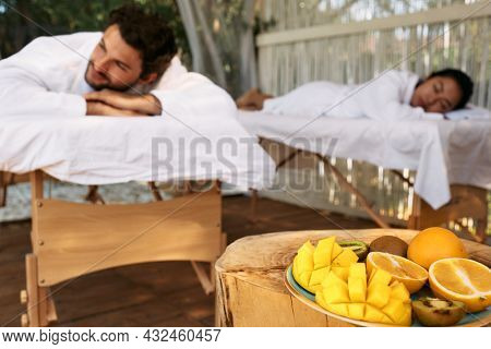 Couple Lying On Massage Tables While Day-spa And Romantic Weekend With Exotic Fruits At Spa Resort.