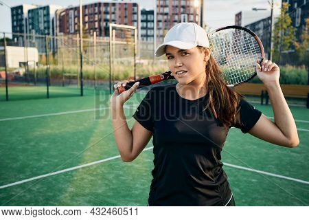 Portrait Of Beautiful Female Tennis Player With Tennis Racket On City Tennis Court In Summer On A Su