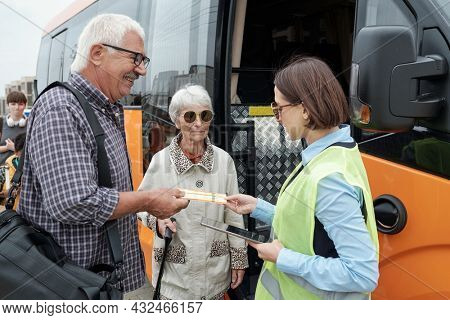 Senior Caucasian couple standing at open bus door and showing tickets to bus supervisor with tablet