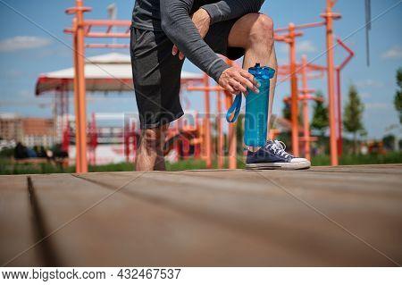 Unrecognizable Male Athlete Legs On A Sports Field, Sportsman Taking A Bottle With Water , Rehydrati