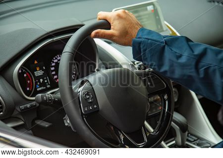 Male Hand On The Steering Wheel Of A Modern Car. Multifunction Steering Wheel And Driver's Panel. No