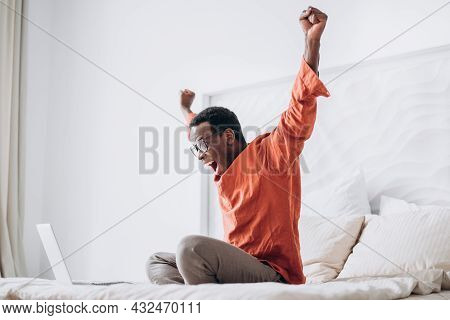 Joyful African-american Guy In Casual Clothes And Glasses Puts Hands Up Sitting Near Open Laptop On