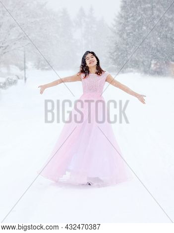 Biracial Teen Girl In Pink Formal Long Gown Outdoors Walking In The Snowfall