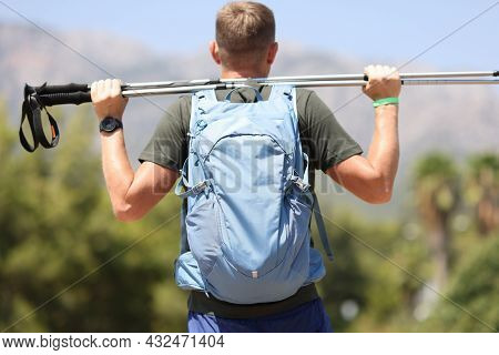 Man With Backpack Looking At Mountains And Holding Walking Sticks In His Hands Back View