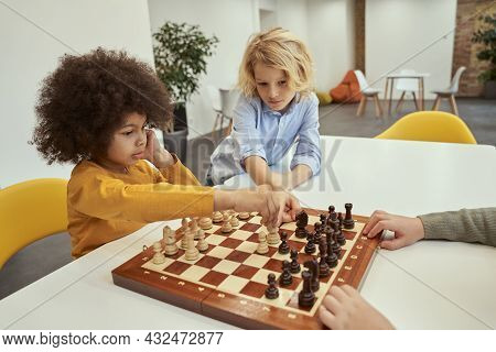 Give Advice. Clever Little Boys Discussing Move While Sitting At The Table And Playing Chess In Scho
