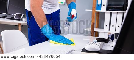 Office Cleaning Service. Janitor Spraying Desk. Workplace Hygiene