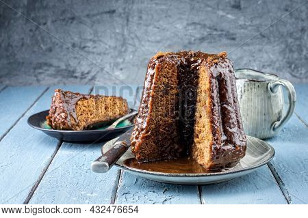 Traditional English sticky toffee pudding with caramel glaze served as close-up on a design plate