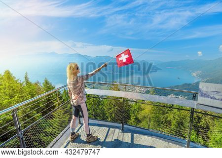 Woman With Swiss Flag On Cardada-cimetta Mount Overlook In Switzerland. Skyline Of Locarno On Cardad