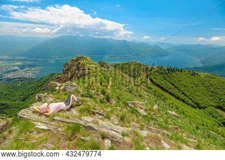 Woman Relaxing On Top Of Cardada-cimetta Mount In Switzerland. Skyline From Swiss Cable Car Of Locar