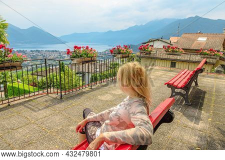 Woman Sitting On Top Of Lake Maggiore In Switzerland. Swiss Bench At Aerial View From Orselina Of Lo