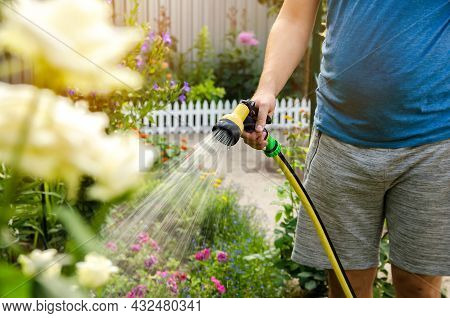 A Gardener With A Watering Hose And A Sprayer Water The Flowers In The Garden On A Summer Sunny Day.