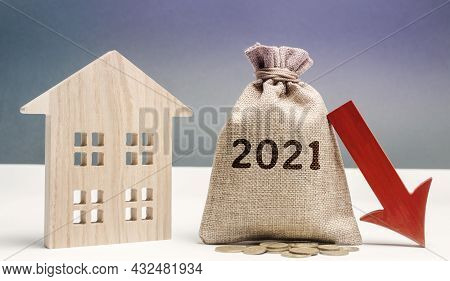 Wooden House And 2021 Money Bag With Down Arrow. Forecasting The Real Estate Market Concept. Interes