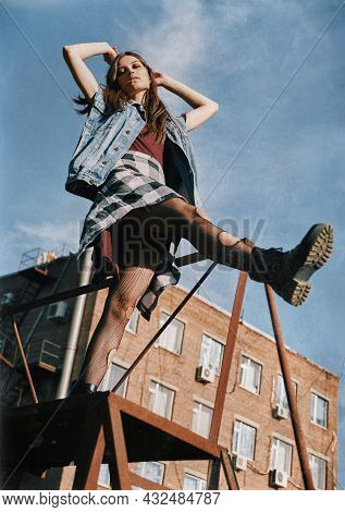 Beautiful Grunge (rock) Girl Takes A Step Down The Stairs. Informal Model Dressed In Jean Jacket, Ch