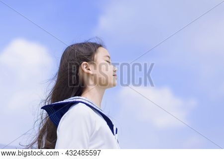 Side View Of Student Girl Enjoying Summer Breeze , Smiling With Eyes Closed