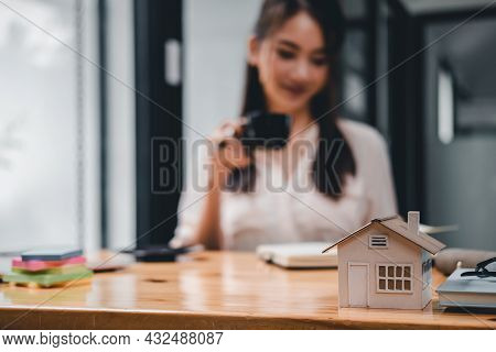 Real Estate Woman With House Model On Working Desk For Investment To Buying Property - Selective Foc