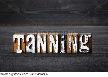 Tanning. White Wooden Letters On A Dark Wooden Background