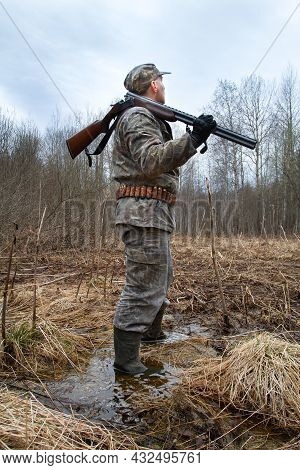 A Woodcock Hunter Stands In A Wet Clearing In A Spring Forest. The Evening Twilight Deepens. The Hun