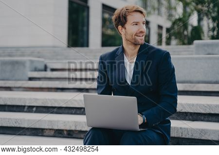 Smiling Brown-haired Neat Unshaven Office Worker In Stylish Suit Sitting Outside On Stairs In City C