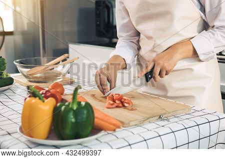 Housewife Using Knife And Hands Cutting Tomato On Wooden Board In Kitchen Room.