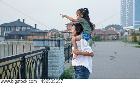 Young Mommy In White T-shirt Carries Little Asian Daughter On Shoulders Walking Along City Embankmen