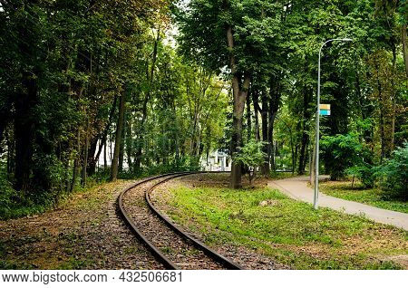 Railroad Track Winding Through The City Park. Scenic Landscape View Of C Track Of Narrow Guage Railw