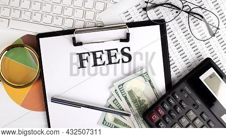 Text Fees On Office Desk Table With Keyboard, Dollars,calculator ,supplies,analysis Chart On White B