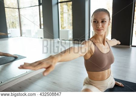 Beautiful Young Slim Sportive Woman In Sportswear Doing Yoga Exercise On Gray Mat At Yoga Sport Cent
