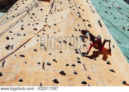 Hard Level. Young Man Professional Rock Climber Practicing At Training Center In Sunny Day, Outdoors